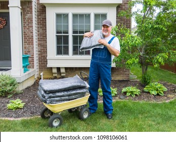 Man unloading bags of mulch from a wheelbarrow in front of his house to spread on a neat cleaned flowerbed behind him during spring