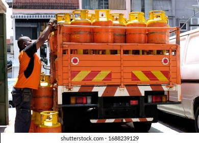 A man unloading canisters of cooking gas from a supply truck parked on a side street to deliver to restaurants and businesses in the area. A Indian worker hauling LPG cylinders off a delivery truck.