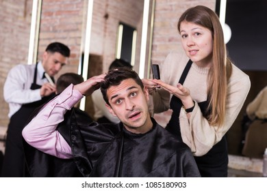 Man unpleasantly surprised by haircut from young woman hairdresser expressing regret in salon