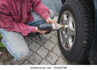 man unscrew wheel nut with an electrical wheel brace tool for to change the tire. seasonal work