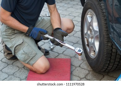 man unscrew wheel nut of the tire manually