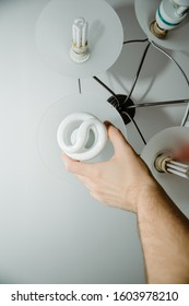 The man unscrews or screws in the light bulb. Bulb replacement concept, big bulb burned.