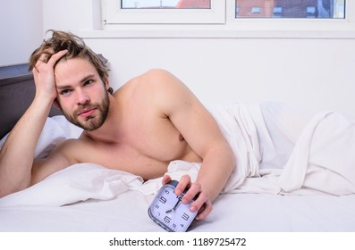 Man unshaven bearded wakeful face having rest. Stick schedule same bedtime wake up time. Enough sleep for him. Regulate your bodys clock. Sleep regime habit. Man unshaven lay bed hold alarm clock.