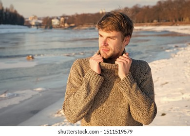 Man unshaven handsome hipster in knitwear sweater high collar stand frozen river background. Winter landscape beauty. Man enjoy winter sunny day. Winter knitted clothes warming up. Winter fashion.