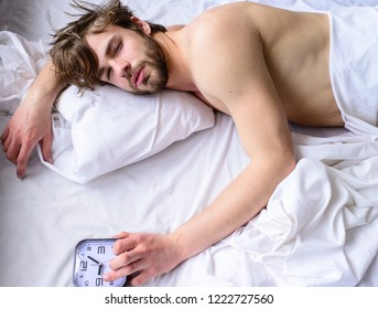 Man unshaven sleepy face lay pillow alarm clock top view. Manage proper regime tips. Toughest part of morning simply getting out of bed. Guy sleep missed alarm clock ringing. Oversleep problem.
