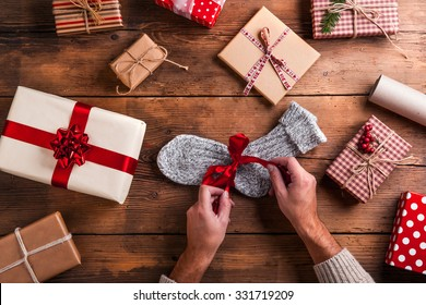 Man unwrapping Christmas present laid on a wooden table background