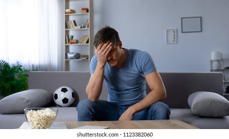 Man upset about defeat of football team, watching tv broadcast, unhappy fan