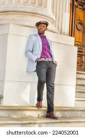 Man Urban Fashion. Wearing a Newsboy cap, dressing in light gray blazer, patterned pink, black under shirt, black pants, brown leather shoes, a young guy is leaning back on a column, relaxing.