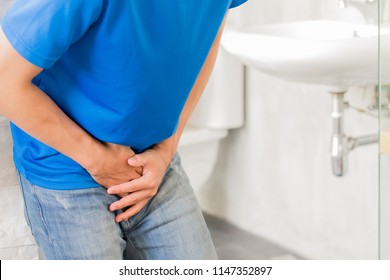 man with urine urgency in the toilet