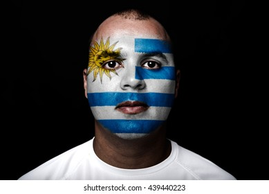 Man with Uruguay flag painted on  his face on black background