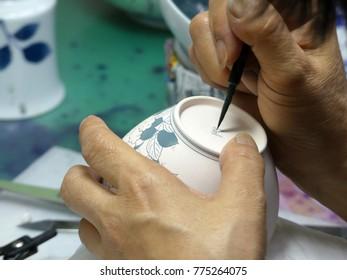 Man use brush painting ceramic cup