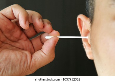 Man use cotton bud swab to clean to clear ear wax Harmful for ear