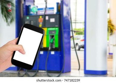 Man use credit card with blur image of gas station as background.