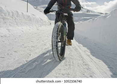 man use electric bicycle, e-bike, ebike, pedal on snow covered road, downhill mountain, bike with wide wheels to go on snow, called fatbike, winter, cold, alps, Simplon Pass, Switzerland