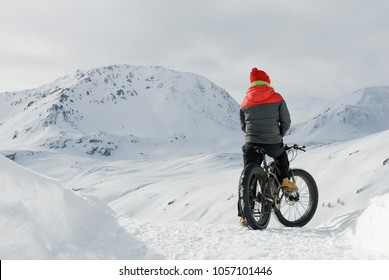 man use electric bicycle, e-bike, ebike, snow covered road, look mountains and horizon, bike with wide wheels to go on snow, called fatbike, winter, cold, alps, freeride, Simplon Pass, Switzerland