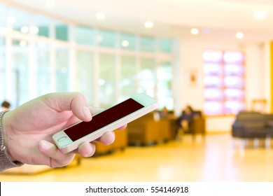 Man use mobile phone, beautiful bokeh of office as background.