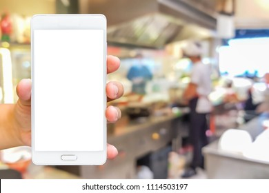 Man use mobile phone, blur images of chef cooking in the restaurant as background.