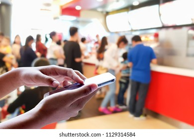Man use mobile phone, blur image of people stand to buy fast food as background.