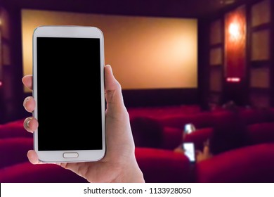 Man use mobile phone, blur image of inside the movie theater as background.