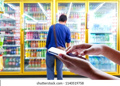 Man use mobile phone, blur image of laborer are looking for the drinks they need in beverage cooler.
