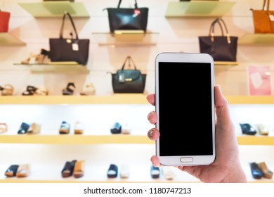 Man use mobile phone, blur image of inside the bag and shoes store as background.