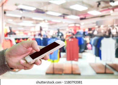 Man use mobile phone, blur image of clothing stores as background.