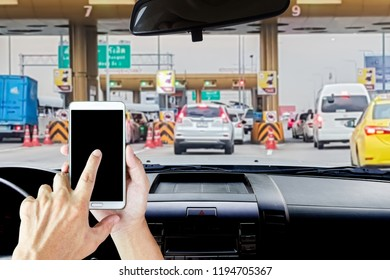 Man use mobile phone, blur image of cars on expressways at expressway payments area as background.