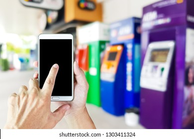 Man use mobile phone, blur image of ATM machine as background.