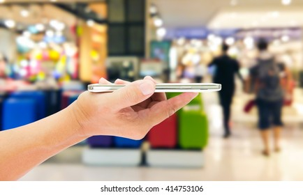 Man use mobile phone, blur image of luggage shop as background.