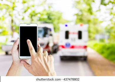 Man use mobile phone, blur image of accident on the road as background.