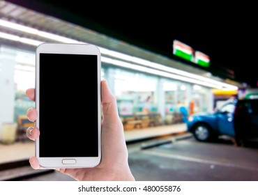 Man use mobile phone, blur image of outside the convenience store as background.