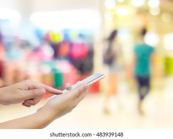 Man use mobile phone, blur image of inside the mall as background.