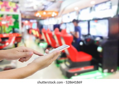 Man use mobile phone, blur image of game zone in the mall as background.