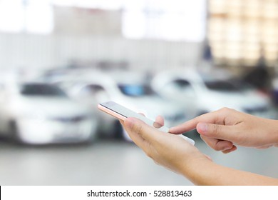 Man use mobile phone, blur image of white cars as background.