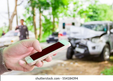 Man use mobile phone ,blur image of accident on the road as background.