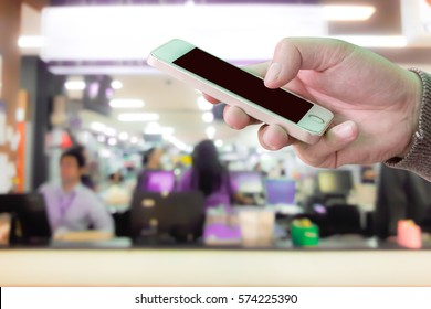 Man use mobile phone, blur image of counter service as background.