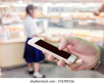Man use mobile phone, blur image of bakery shop as background.