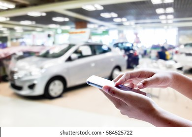 Man use mobile phone, blur image of car showroom as background.