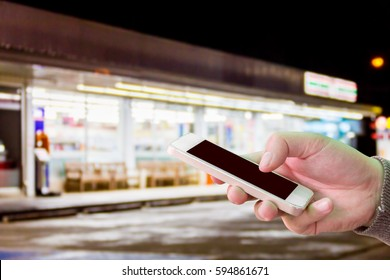 Man use mobile phone, blur image of convenience store at night as background.