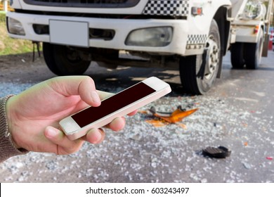 Man use mobile phone, blur image of car accident as background.