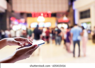 Man use mobile phone, blur of people in the movie ticket line as background.