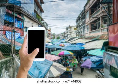 Man use mobile phone, blur image of street market as background.