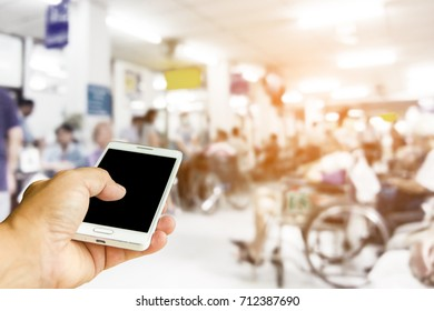 Man use mobile phone , blur image of inside the hospital as background.(On vintage tone.)