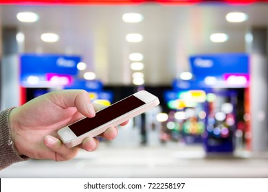 Man use mobile phone, blur image of gas station at night as background.