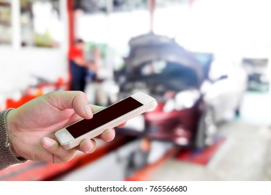 Man use mobile phone, blur image of inside the garage as background.