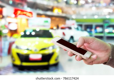 Man use mobile phone, blur image of the new car show as background.