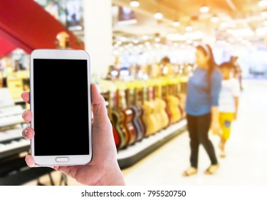Man use mobile phone, blur image of guitar shop in the mall as background.
