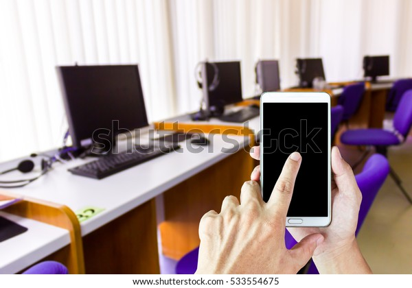 Man use mobile phone, blur image of computer training room as background.