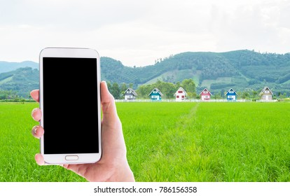 Man use mobile phone, the colorful small houses on field as background.
