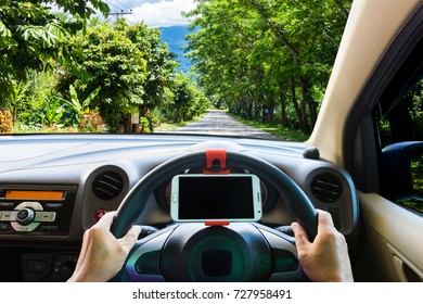 Man use mobile phone while driving, The road is full of trees along the way as background.